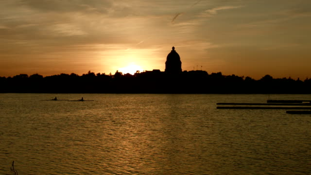 Sunset rowing on lake in front of government building video