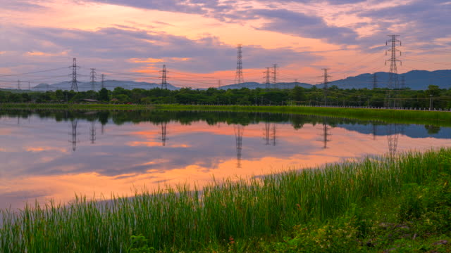 sunset scene timelapse of electrical power line grid with reflection of water - sottostazione elettrica video stock e b–roll