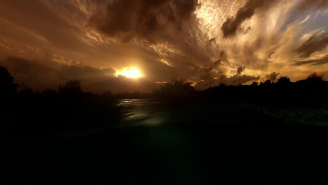 Sunset seen from water level green light rays underwater video