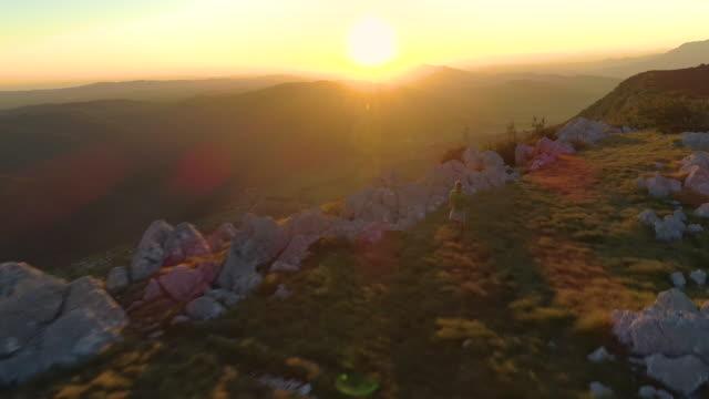 bländning: solnedgången lyser på den manliga idrottare löper längs natursköna gräsbevuxen väg. - jogging hill bildbanksvideor och videomaterial från bakom kulisserna