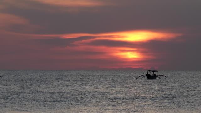 vídeos y material grabado en eventos de stock de puesta de sol foto de un barco de pesca en la playa de kuta en bali - anclado