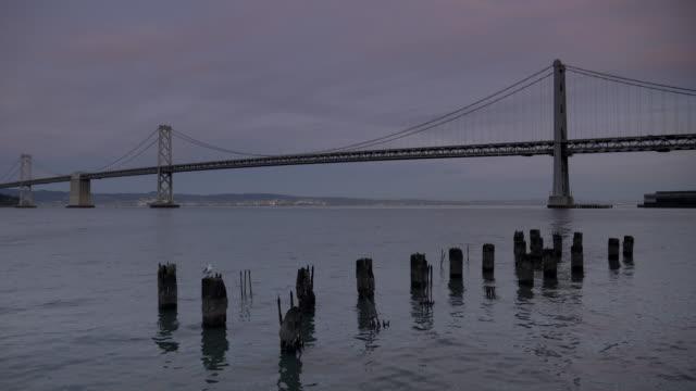 vídeos y material grabado en eventos de stock de tiro al atardecer de viejos pilones y el puente de la bahía en san francisco - oakland