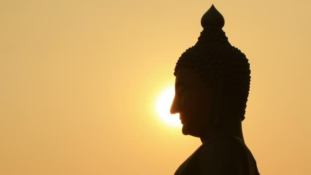 Sunset side big buddha statue silhouette video
