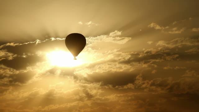 Sunset Silhouette Hot-Air Balloon Silhouette hot-air balloon traveling through golden clouds at sunset. hot air balloon stock videos & royalty-free footage