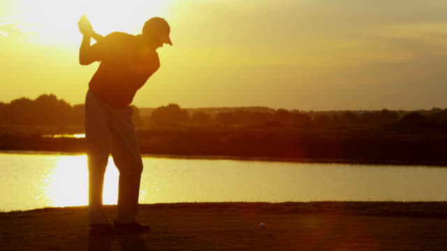 Sunset silhouette male Caucasian professional golfer teeing off video