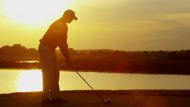 Sunset silhouette male golfer teeing off on fairway video