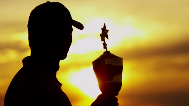 Sunset silhouette of golf tournament winner holding trophy video