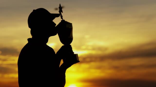 stockvideo's en b-roll-footage met zonsondergang silhouet van golf toernooiwinnaar trofee te houden - kampioenschap