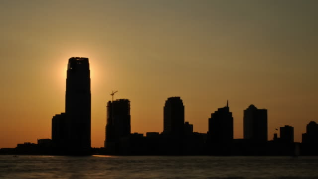 Sunset Silhouette over buildings and water - Med Shot video