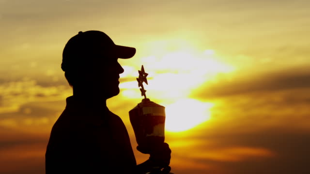 Sunset silhouette successful male golfer holding winning trophy video