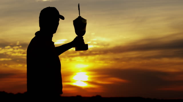 Sunset silhouette winning professional male golfer with trophy video