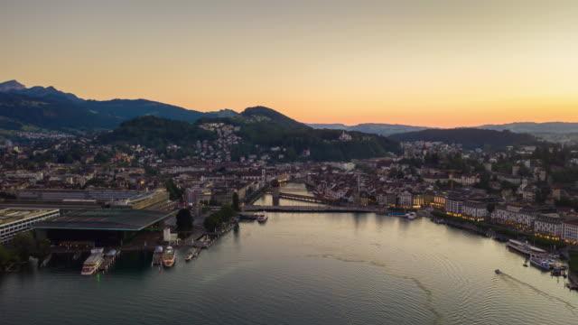 sunset sky flight over luzern cityscape lakeside bay aerial panorama 4k timelapse switzerland - vídeo