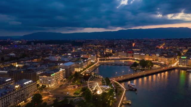 sunset sky night illuminated geneva city lakeside aerial panorama 4k timelapse switzerland - vídeo