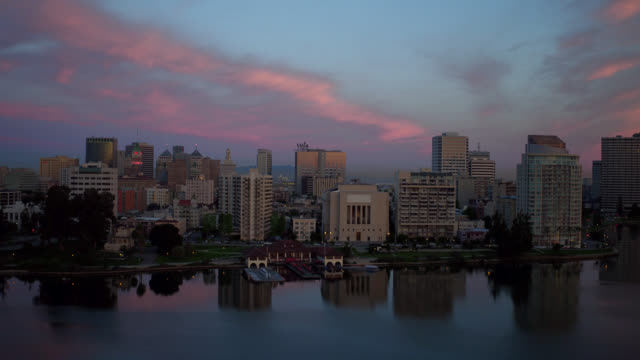Sunset skyline Aerial tracking shot of Oakland skyline at sunset over Lake Merritt. oakland stock videos & royalty-free footage