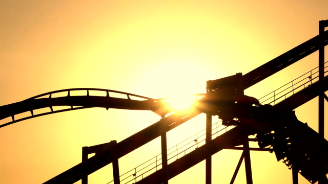 SLOW MOTION: Sunset sun shining through extreme roller coaster ride video