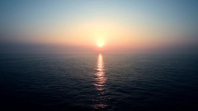 vídeos de stock e filmes b-roll de sunset sunrise on calm sea, view from open deck of moving cruiser - linha do horizonte sobre água