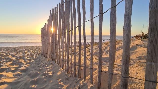 Sunset sun's rays peeking through a wooden fence on a sandy beach Sunset sun's rays peeking through a wooden fence on a sandy beach moving clip. France, Lacanau-Ocean, Europe, beach by Atlantic Ocean. coastal feature stock videos & royalty-free footage