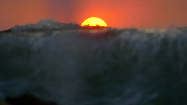 Bидео sunset the sun through the waves of the storm