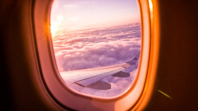Sunset through airplane window Looking through airplane window at orange lit clouds and sky. plane stock videos & royalty-free footage