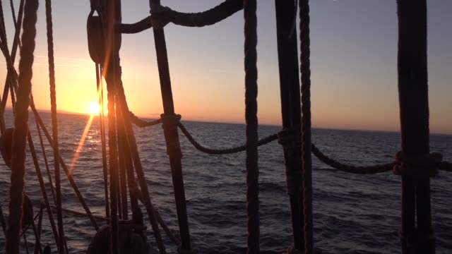 Sunset through the shrouds and rigging of an old sailing ship. Seascape slow motion video.