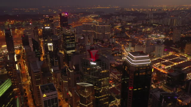 sunset time illuminated flight over singapore city downtown rooftops aerial panorama 4k - vídeo