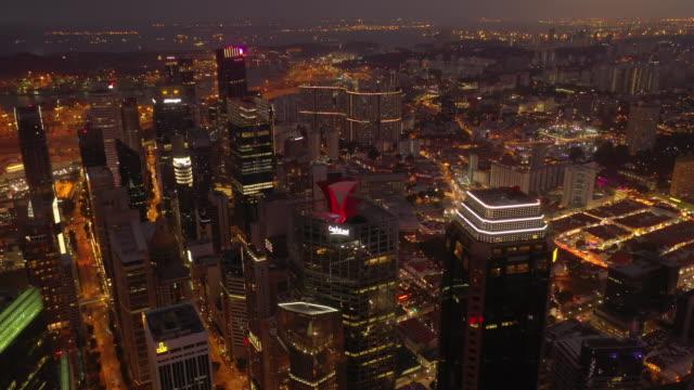 heure du coucher du soleil illuminé vol au-dessus de singapour ville du centre-ville toits panorama aérien 4k - Vidéo