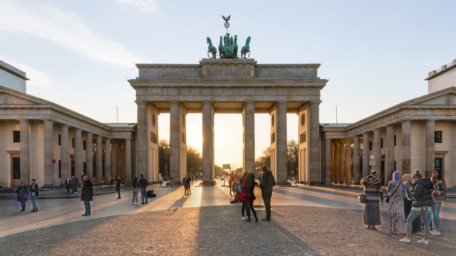 sonnenuntergang am berliner brandenburger tor mit touristen und schatten - berlin brandenburger tor blurred stock-videos und b-roll-filmmaterial