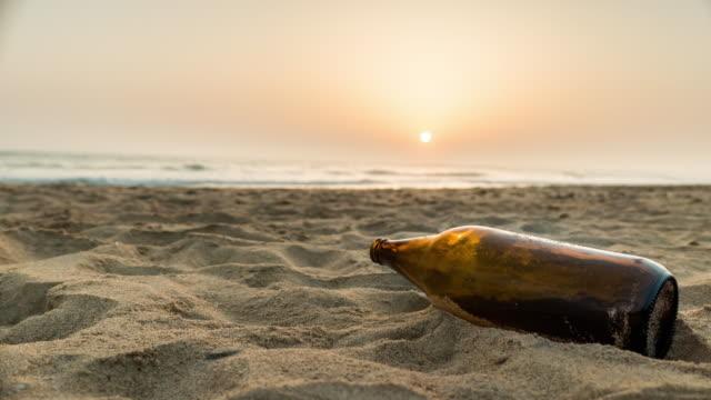 timelapse atardecer con botella de cerveza en la arena en la playa de Cádiz españa - vídeo
