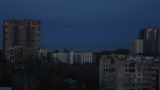 Sunset to night time lapse over urban skyline near waterfront Sunset to night transition time lapse aerial view of hi-rise apartment buildings. European city view while getting dark. Cityscape timelapse at urban seaside with moving vessel on background ocean front properties stock videos & royalty-free footage