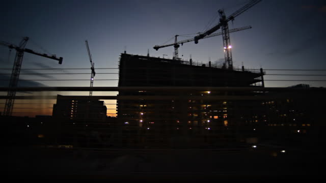 sunset train ride with silhouette cranes #1 - billboard train station bildbanksvideor och videomaterial från bakom kulisserna