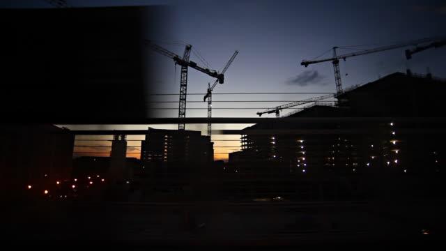 sunset train ride with silhouette cranes #3 - billboard train station bildbanksvideor och videomaterial från bakom kulisserna