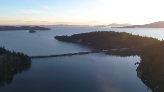 sunset train water crossing san juan islands washington state usa bellingham bay aerial 4k drone flight - ocean spokojny filmów i materiałów b-roll