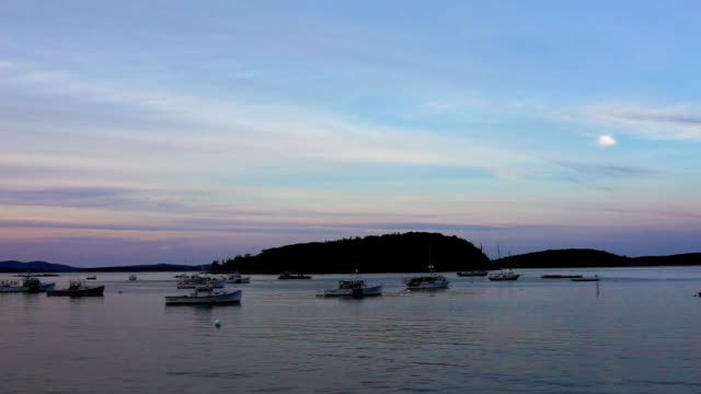 Sunset, twilight, dusk in Bar Harbor, Maine village marina with empty boats in water with colorful pink sky video