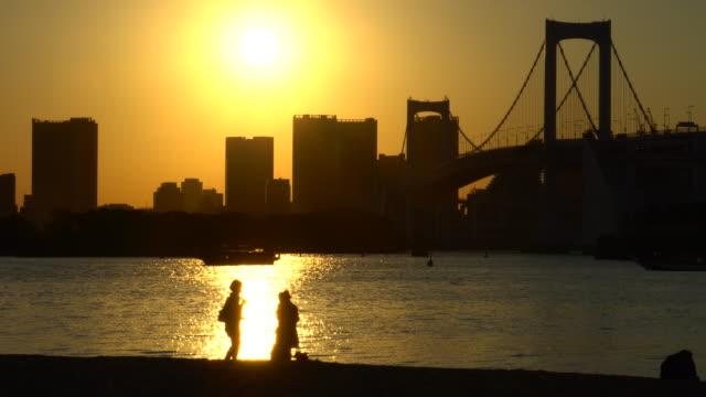 vídeos de stock e filmes b-roll de sunset view from odaiba / couple - frente ao mar