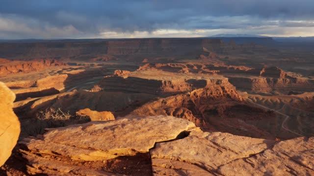 vista al tramonto del dead horse point state park, utah, usa. сamera si muove su una scogliera, vista sul canyon e sul fiume colorado. colpo steadicam, 4k - canyon video stock e b–roll