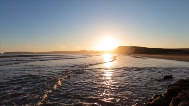 Sunset view of Drakes Beach, the sunlight reflected on the water surface and the wet sand, Point Reyes National Shoreline, California