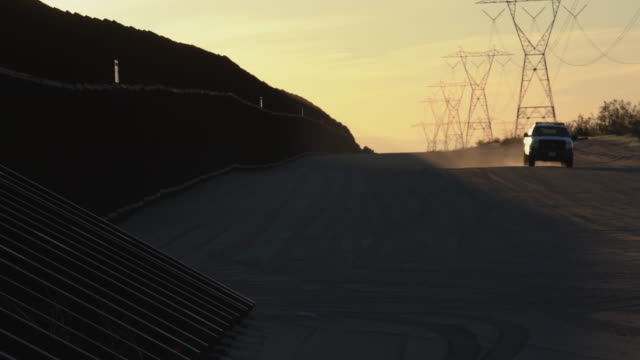 A Sunset View Of The International Border Wall, An Agent Patrolling,California, United States Side