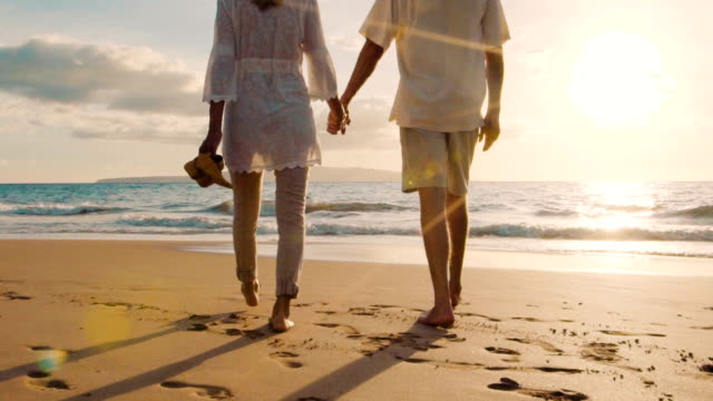 Sunset Walk on a Luxury Beach. Happy Retired Couple on Tropical Vacation.