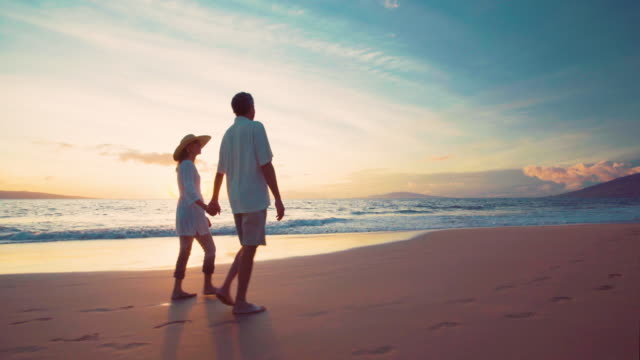 Sunset Walk on a Luxury Beach. Happy Retired Couple on Tropical Vacation. video