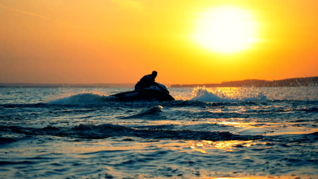 Sunset waterscape with a man jet-skiing.