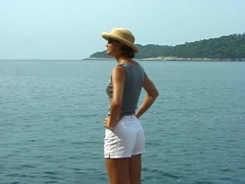 stockvideo's en b-roll-footage met suntanned / sun tan woman looks at water view - handen op de heupen