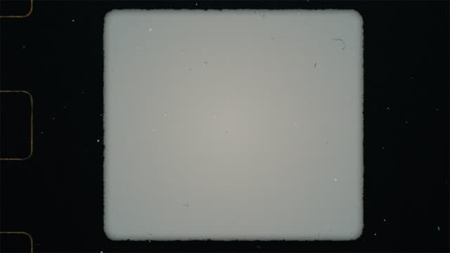 vidéos et rushes de super 8mm film frame scan avec trou sprocket, carré format 3x4 cadre. fuites lumineuses et superposition abstraite de texte orange. pour un look vintage rétro. grain de bruit et rayures texture transparente. bords déchirés - bordure