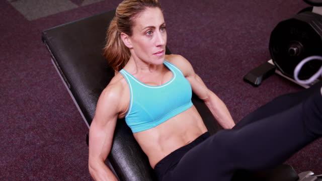 bardzo pasuje kobieta za pomocą nogi waga maszyny - biustonosz sportowy filmów i materiałów b-roll
