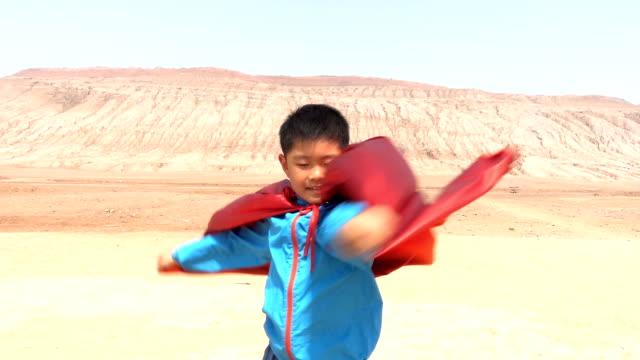 Super hero playing in Flaming Mountain, Turpan Super hero playing in Flaming Mountain, Turpan cape garment stock videos & royalty-free footage