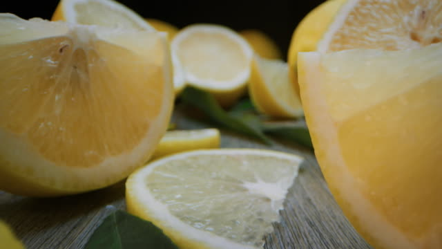 super macro slide shot of lemons on a wooden bench, in slow motion. - лимон стоковые видео и кадры b-roll