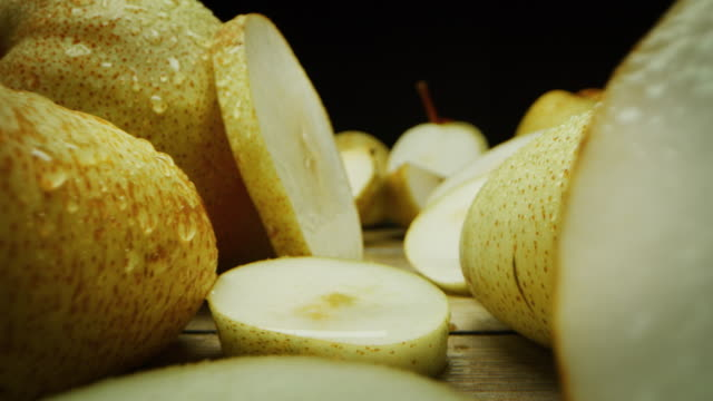super macro slide shot of pears on a wooden bench, in slow motion.