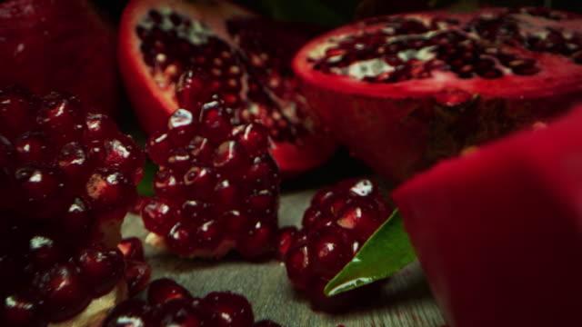 vídeos de stock e filmes b-roll de super macro slide shot of pomegranate on a wooden bench, in slow motion. - romã