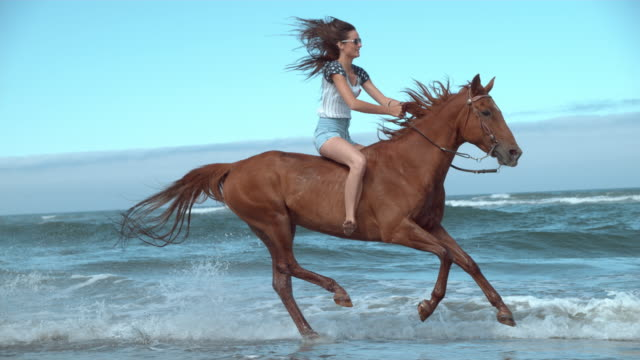 Super slo mo woman riding horses at beach