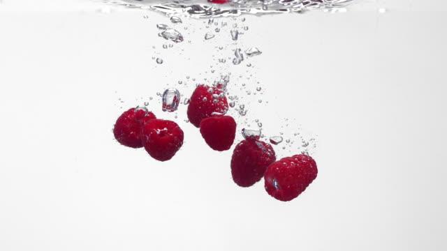 vídeos y material grabado en eventos de stock de super slow mo of raspberries falling into water - frambuesa