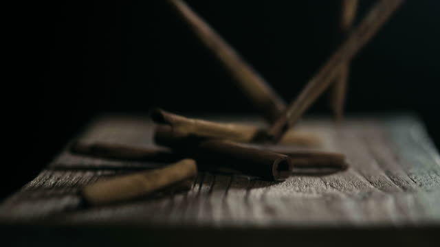 Super slow motion : A cinnamon stick falls on a black